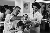 Young boy getting his first haircut from a barber while his mother looks on.   Image was taken in the 1950's.