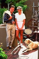 Couple relaxing after tennis with dog.
