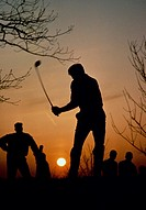 Silhouette of a man swinging at a golf ball at sunset while other players look on.