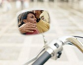 Couple embracing, view through wing mirror on moped