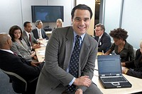 Businessman perched on conference table in meeting, smiling, portrait
