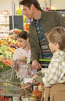 Father and children (8-10) shopping in supermarket