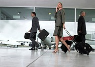 Business people walking through airport with luggage, ground view