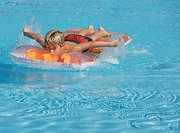 Boy (6-8) paddling on inflatable raft in swimming pool