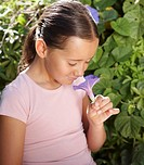 Girl (6-8) smelling petunia flower, outdoors, close-up
