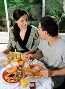 Couple at table eating breakfast, smiling at each other, elevated view