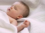 Baby girl (6-9 months) sleeping under blanket, close-up