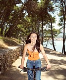 Teenage girl (16-18) riding bicycle on coast path, smiling, portrait