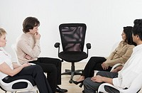 Businesspeople Staring at Empty Chair
