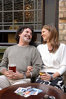 Mature couple relaxing outside pub, smiling, postcards on table