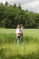 Young man carrying woman piggyback in meadow, rear view