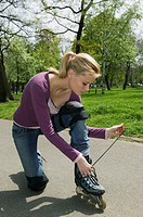 Young woman kneeling on path in park tying laces on on roller skates