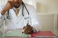 Doctor making notes on medical records (thumbnail)