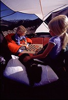 Two sisters and their puppy playing a game of checkers while camping on Mount Judah, CA.