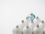 Blue Christmas Tree Ornament in Front of White Ornaments