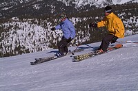 A couple skiing on a groomed ski run at Diamond Peak, NV.