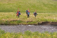 Three skiers hiking in grass on Umnak Island inthe Aleutian Islands Alaska.