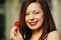Young woman holding strawberry, smiling, portrait, close-up