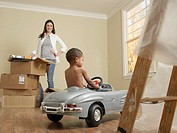 Mother with Boy Driving Little Car on Moving Day