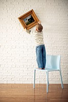 Boy Standing on Chair Hanging Painting on Wall