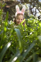 Girl Peeking Up in Grass Wearing Bunny Ears