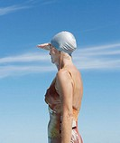 Mature woman wearing swimming hat shielding eyes from sun, side view