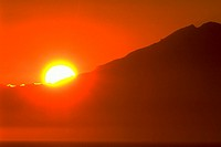 A bright orange sun sets behind Mount Redoubt at Cook Inlet in Ninilchik, Alaska.