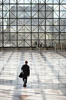 Businessman Walking Across Empty Lobby