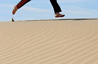 Feet running over sand dune. Death Valley, California. USA.