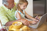 Girl Using a Laptop with Her Grandfather During Breakfast