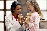 Physician Demonstrating a Tongue Depressor on a Teddy Bear