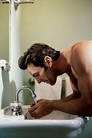 Side profile of a young man washing his face in a bathroom sink