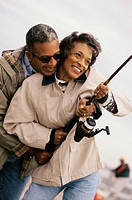 Mature couple holding a fishing rod