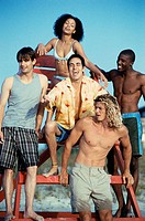 Four young men and a young woman sitting on a lifeguard chair on the beach