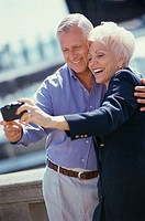 Senior couple taking a photograph of themselves