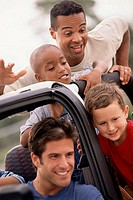 Close-up of two fathers with their sons in a jeep