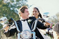 Low angle view of a newlywed couple riding a motorcycle
