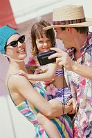 Close-up of parents with their daughter taking a photograph of themselves