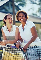 Two mid adult women leaning against a tennis net