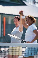 Two mid adult women cheering after winning a match