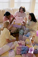 Four women opening gifts at a baby shower