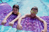 Portrait of a boy and a girl leaning on a pool raft in a swimming pool