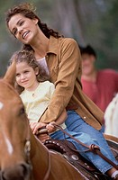 Mother and daughter riding a horse