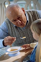 Close-up of a grandfather feeding his grandson