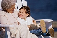 Grandmother sitting with her granddaughter and smiling
