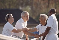 Side profile of two senior couples shaking hands on a tennis court