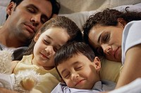 Close-up of parents with their two children sleeping on the bed