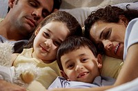 Close-up of parents with their two children lying on the bed