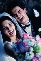 Close-up of a newlywed couple laughing