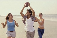 Two teenage couples playing football on the beach